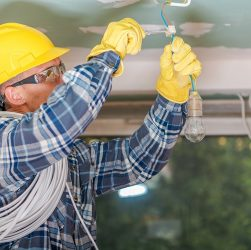 Caucasian Electrician in Yellow Safety Hard Hat at Work. Reinstallation of Residential Electrical System.