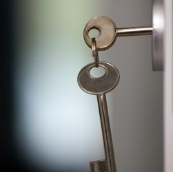 Close-up shot of keys in the keyhole. Locking or unlocking the door