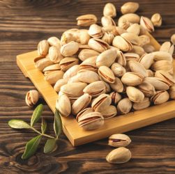 pistachios-on-a-plate-leaves-and-wooden-background-close-up-copy-space-background-brown-closeup_t20_jREKxr