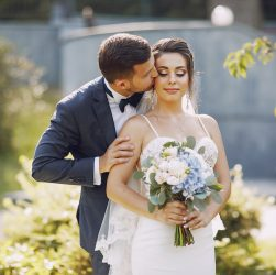 A young and beautiful bride and her husband is standing in a summer park with bouquet of flowers