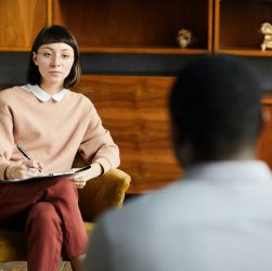 Young woman sitting on armchair during her psychology therapy and talking to psychologist